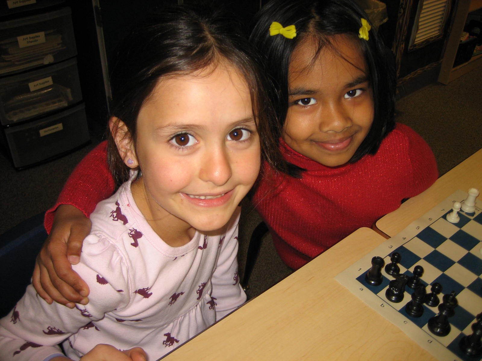 Two smiling students and a chess board