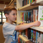 Elementary student pulling book off library shelf